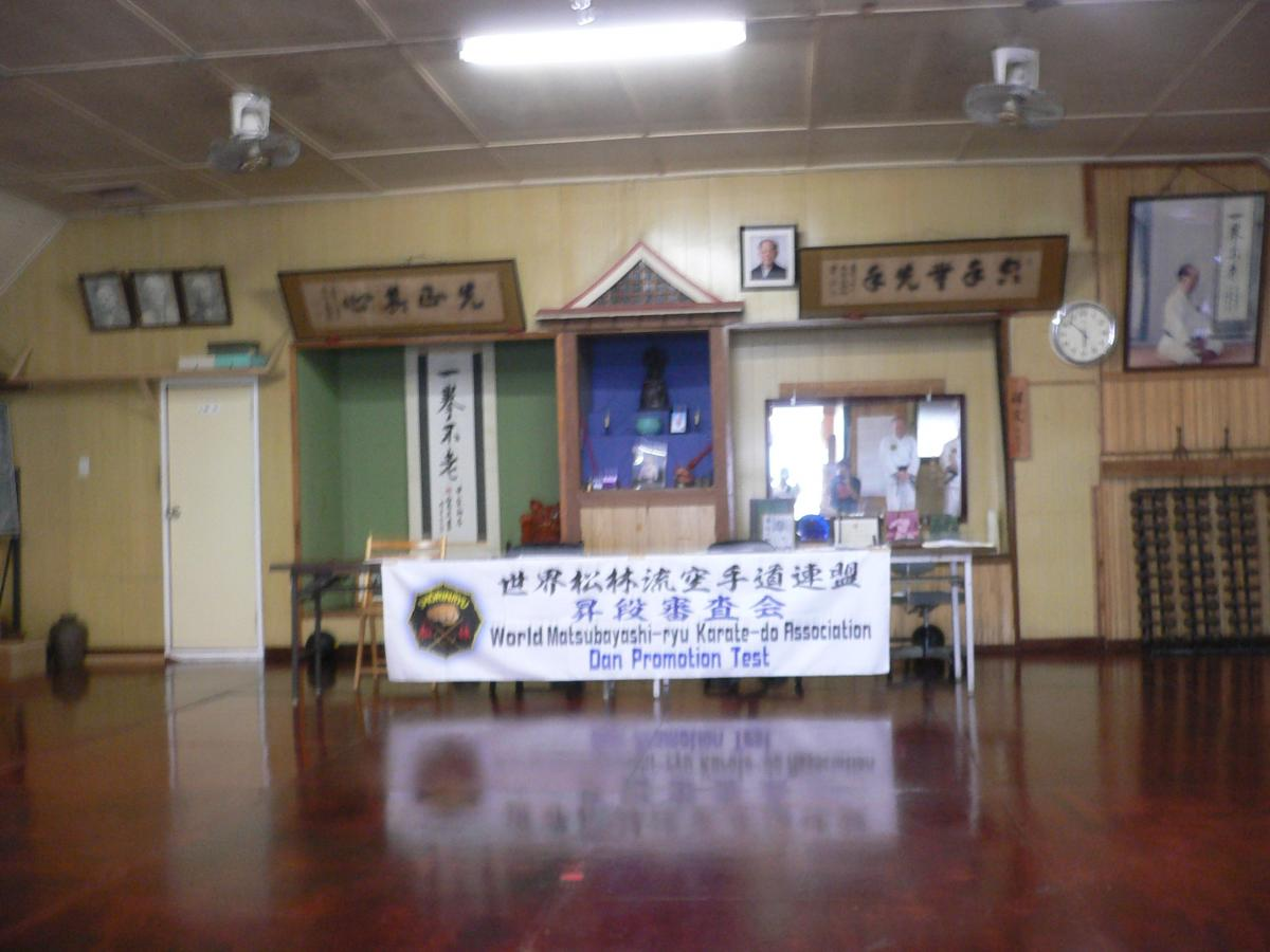 "Nagamine Karate Dojo, the birth place of the WMKA. You can see the Grand Master 1st Soke Shoshin Nagamine with ""心其正先First purify your mind and手先無手空There is no first attack in karate"" on both sides on the front wall."